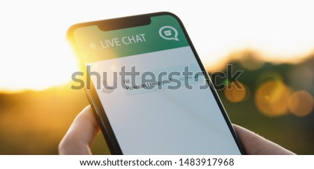 Person use customer service and support live chat with chatbot and automatic messages or human servant outdoor. Assistance and help with mobile phone app. Smartphone helpdesk for feedback cell.