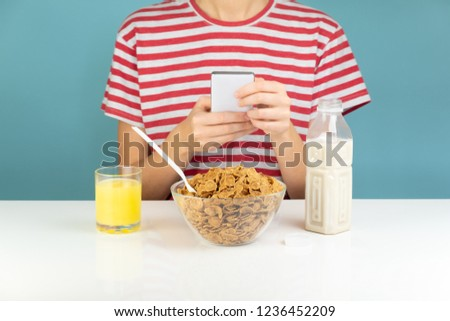 Person uses phone at breakfast table, minimalistic illustrative concept. Browsing social media while eating healthy whole grain cereal  with juice and milk #1236452209