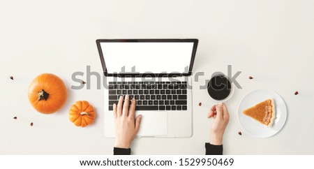 Person using a laptop computer with pumpkins - overhead view #1529950469