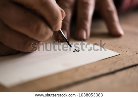 Person using a nib pen and ink to do calligraphy in a close up view of his hands and the first letter drawn on the paper. #1038053083