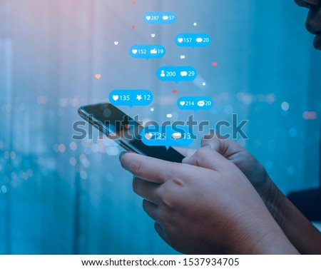 Person using a social media marketing concept on mobile phone with notification icons of like, message, comment and star above mobile phone screen.