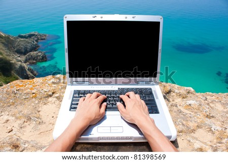 Person using laptop at beautiful location by the sea