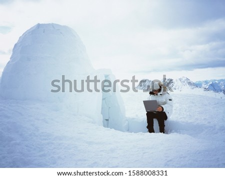 Person using laptop next to igloo
