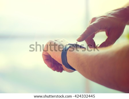 Person using smart watch. Young man making gestures on a wearable smart watch computer device, smartwatch close up (unrecognizable)