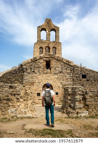 Person visiting a Romanesque church, man with backpack in front of an ancient building made of stone, Santa Helena de Rodes, Port de la Selva, Girona, Spain. Vertical picture Stock fotó ©