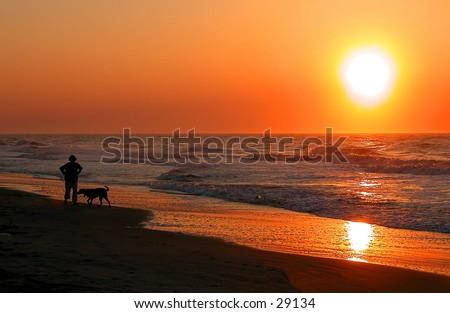 Person laufend ein Hund an Sonnenaufgang entlang der Südkarolina Küste
