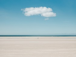 Person walking alone far away on the beach with a single cloud above on a blue sky