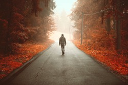 Person walking alone on artistic orange colored rural foggy road.