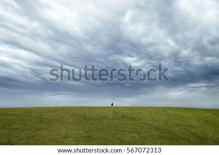 Person walking on the horizon with dark dramatic sky behind.