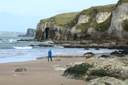 Person walking on Whiterocks Beach with backdrop of cliffs and coastline visible, Portrush, County Antrim, N. Ireland