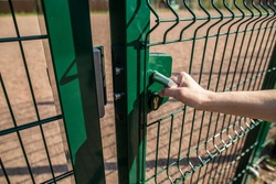person wants get in on playground through the little gate of the welded wire mesh is green, wonderful spring sunny day