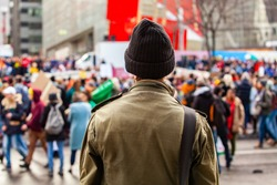 Person watches environmental protest. A young guy wearing a green coat is viewed from behind, watching environmentalists march in the city center of Montreal, Canada