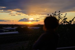 Person watching a dramatic orange sunset with the fiery sun low over the horizon in a cloudy sky in an over the shoulder view over countryside