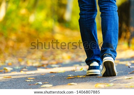 Person wearing casual sneakers shoes and blue jeans trousers walking outdoor. Stylish urban fashion details. #1406807885