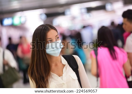 Person wearing protective mask against transmissible infectious diseases and as protection against pollution and the flu. Asian woman commuter in airport public area. #224569057