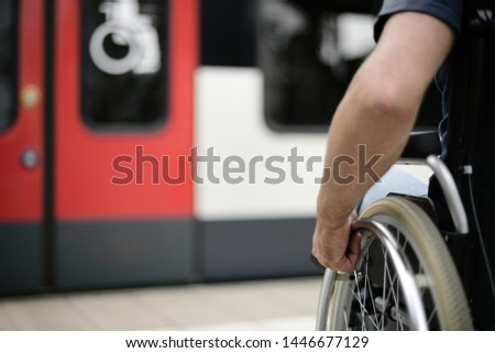 Person wheelchair user at station at barrier free accessibility compartment  sign mobility transport Stock foto ©