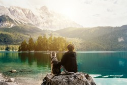 person with a dog in the mountains at a beautiful lake at sunset. Traveling with a pet. Happy satisfied time together. Friendship between man woman and dog. hugs.