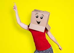 Person with cardboard box on its head dancing hilariously and sticking a finger up in the air on yellow background