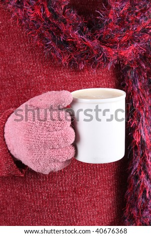 Person with pink mittens, scarf and sweater holding a warm beverage in a white cup on a cold winter day