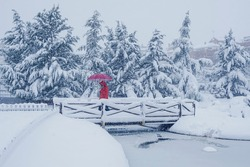 Person with red clothes and umbrella walking on an icy bridge with snow.