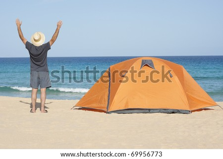 person with tent  enjoying camping recreation at a wonderful tranquil beach