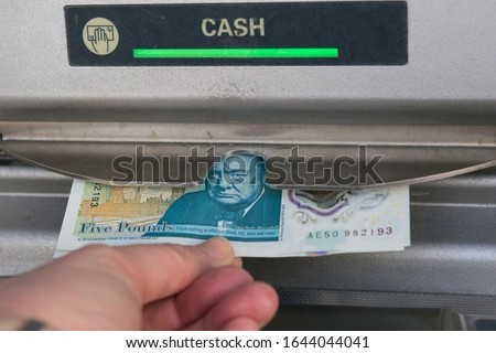 Person withdrawing money from UK United Kingdom cash machine ATM withdrawal hand holding five pound note. British economy visiting England British Tourism concept idea