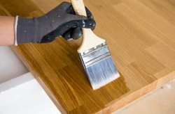 Person working, oiling kitchen countertop before using, brushing oiling with linseed oil. Solid wood butcherblock countertop maintenance concept. Home indoors.