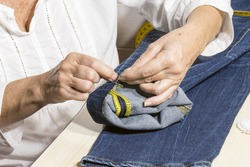 person working,seamstress woman sews the bottoms of the pants