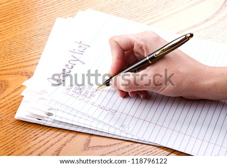 person writing grocery list