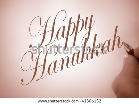 Person writing Happy Hanukkah in calligraphy with  sepia tone