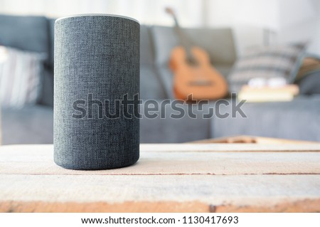 Personal assistant connected loudspeaker on a wooden table in a Smart Home in a living room. Next, a guitar and some books on a sofa. Copy space for Editor's text.