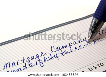 Personal bank check for mortgage payment with pen on white background with copy space.