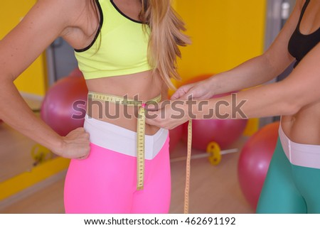 personal coach training measuring his young female client waist