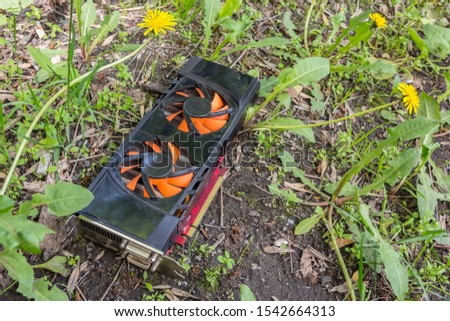 Personal computer graphics card thrown into the grass due to breakage #1542664313