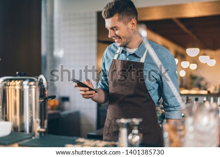 Personal device. Waist up of a happy young man in brown apron standing with a modern smartphone and smiling while looking at the screen of it