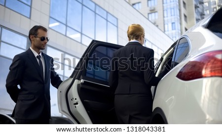 Personal driver waiting for boss on parking lot, helping her to get into car #1318043381