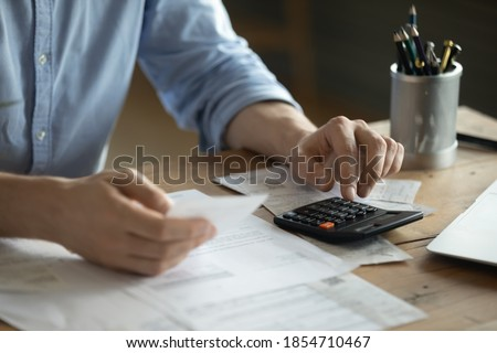 Personal finance management, accounting concept. Close up view man sitting at table using calculator performs arithmetic operations calculates costs per month, manage family budget, control expenses Photo stock ©