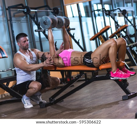 Personal fitness instructor helping a young woman at gym, she exercising with dumbbells.