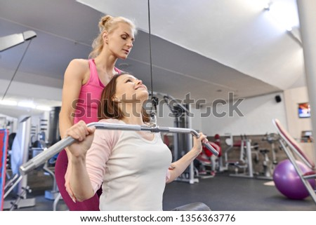 Personal fitness instructor helping summer woman exercising in health club. Health fitness sport age concept.