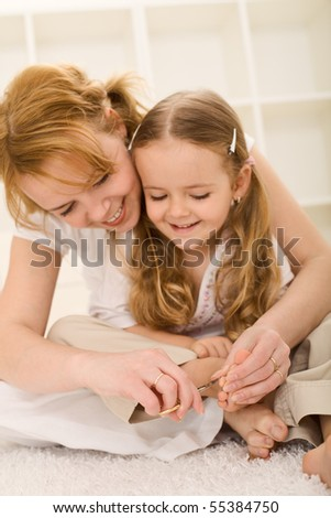 Personal grooming - little girl and her mother cutting nails - focus on fingers