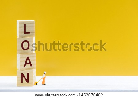 Personal loan / payday loan concept : Miniature worker uses a hand-pull pallet drags square cubes with words LOAN, depicts a sum of long-term money borrowed and expected to be paid back with interest