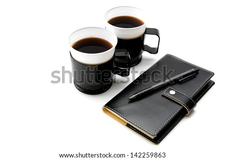 Personal organizer and cup of instant coffee for taking out