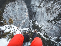Personal perspective of hiker legs hanging above the cliff. Adventure time above Bicaz Gorge, Romania