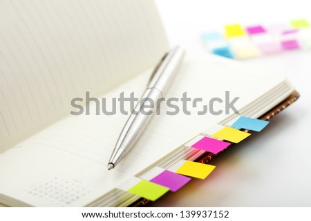Personal planner (organizer) with colorful bookmarks on office desk. Shallow focus.