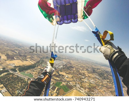 Personal point of view of parachutist flying over a landscape panorama of mountain city and opening his parachute for being ready to land. Skydiver person start landing process during his flight.
