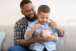 Personal Savings And Budget Planning. African American Daddy And His Son Boy Putting Coin In Piggybank Raising Money Sitting On Couch At Home. Child And Financial Literacy