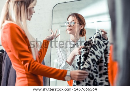 Personal stylist. Red-haired personal stylist wearing glasses listening to her client