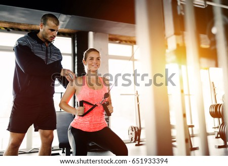 Personal trainer assisting woman lose weight