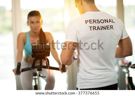 Personal trainer at the gym with client on bike