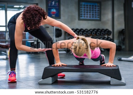 Personal trainer correct her client while doing push-ups.